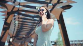 Den attraktiva unga flickan som talar vid telefonen i ett soligt, parkerar stock video