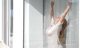 Den attraktiva unga kvinnan öppnar gardiner i ultrarapid ser soluppgånganseendet nära fönstret i henne hem 4K arkivfilmer