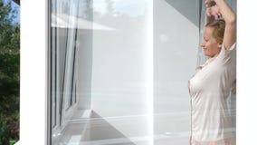 Den attraktiva unga kvinnan öppnar gardiner i ultrarapid ser soluppgånganseendet nära fönstret i henne hem 4K lager videofilmer