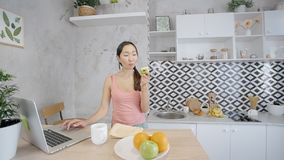 Den attraktiva unga kvinnan använder bärbara datorn som äter äpplet i modernt kök arkivfilmer