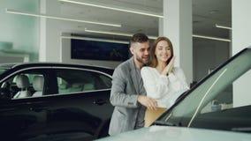 Den attraktiva unga kvinnan får den nya bilen från hennes pojkvän, stänger leder han henne ögon och henne till automatiskn i moto stock video