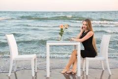 Den attraktiva unga kvinnan i en elegant och svart klänning sitter på en tabell på bakgrunden av havet Fotografering för Bildbyråer