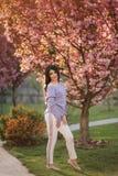 Den attraktiva unga kvinnan i en purpurf?rgad tr?jast?llning av det sakura tr?det i parkerar framme royaltyfri fotografi