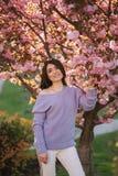 Den attraktiva unga kvinnan i en purpurf?rgad tr?jast?llning av det sakura tr?det i parkerar framme royaltyfria bilder