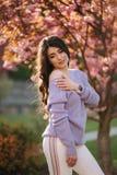 Den attraktiva unga kvinnan i en purpurf?rgad tr?jast?llning av det sakura tr?det i parkerar framme arkivfoto