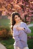 Den attraktiva unga kvinnan i en purpurf?rgad tr?jast?llning av det sakura tr?det i parkerar framme royaltyfri foto