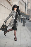 Den attraktiva unga kvinnan i en vinter danar skjutit Härlig trendig ung flicka i svart som poserar på aveny Elegant brunett royaltyfri fotografi