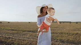 Den attraktiva unga kvinnan i klänning och hatt har gyckel med henne behandla som ett barn i fältet på solnedgången Mamman och so lager videofilmer
