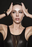 Den attraktiva unga kvinnan i svarta läderkläder trycker på hennes händer till hennes huvud royaltyfri fotografi