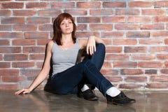 Den attraktiva unga kvinnan i tillfällig kläder, jeans och västgrå färger ser till kameran och ler sammanträde på ett golv Arkivfoto