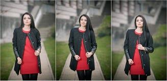 Den attraktiva unga kvinnan i vintermode sköt med byggnad på bakgrund Härlig trendig flicka i svart lag över den röda klänningen Royaltyfri Fotografi