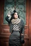 Den attraktiva unga kvinnan i vintermodeskott med smidesjärn dekorerade dörrar i bakgrund. Härlig trendig kvinnlig Arkivfoto