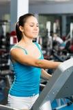Den attraktiva unga kvinnan justerar treadmillen Royaltyfri Foto