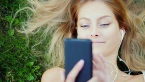 Den attraktiva unga kvinnan ligger på gräs, tycker om smartphonen Hår ligger beautifully på gräsmattan arkivbild