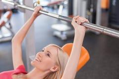 Den attraktiva unga kvinnan lyfter vikt i idrottshall arkivfoto