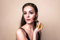 Den attraktiva unga kvinnan med blänker smink och borsten fotografering för bildbyråer