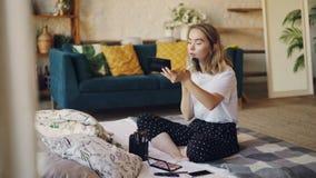 Den attraktiva unga kvinnan med blont hår sätter på sminksammanträde på borstar och skönhetsmedel för säng hemmastadda användande lager videofilmer