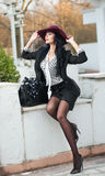 Den attraktiva unga kvinnan med burgundy färgade den stora hatten i höstligt modeskott Härlig dam i svart dräkt med den korta kjo Arkivbild