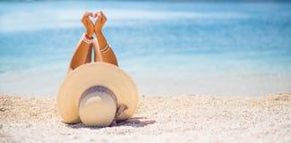 Den attraktiva unga kvinnan med hatten ligger på stranden royaltyfri bild