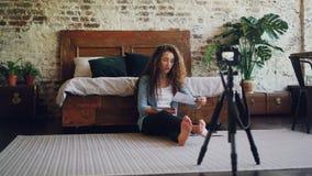 Den attraktiva unga kvinnan med den långa bloggeren för lockigt hår antecknar videoen för hennes internetblogg genom att använda  arkivfilmer