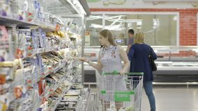 Den attraktiva unga kvinnan med shoppingvagnen väljer den rimmade fisken i supermarket Shopping och folkbegrepp materiel lager videofilmer