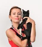 Den attraktiva unga kvinnan rymmer en svart kattunge på händer royaltyfri bild