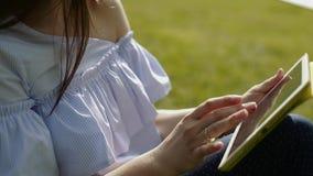 Den attraktiva unga kvinnan sitter på gräs i sommardag arkivfilmer