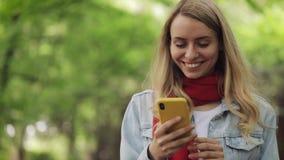 Den attraktiva unga kvinnan som använder smartphonen som går ner, parkerar V?r- eller sommartid stock video