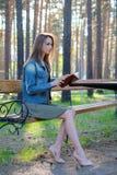 Den attraktiva unga kvinnan som tillfälligt kläs, läser sammanträde för gammal bok på en träbänk i parkera Royaltyfria Bilder