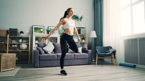 Den attraktiva unga kvinnan squatting hemma göra övningar för viktförlust stock video