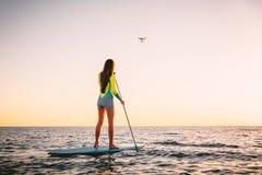 Den attraktiva unga kvinnan står upp skoveln som surfar, och surrhelikoptern med härlig solnedgång färgar Royaltyfri Bild