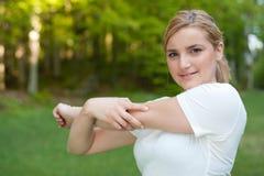 Den attraktiva unga kvinnan sträcker muskler Royaltyfri Fotografi