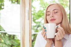 Den attraktiva unga kvinnan tycker om den varma drinken Arkivfoton