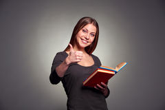 Den attraktiva unga kvinnavisningen tumm upp Arkivfoto