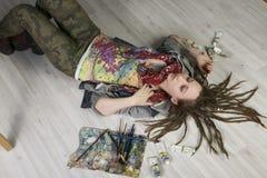 Den attraktiva unga kvinnliga konstnären med dreadlocks ligger på golvet, hållborstar, där är rör med närliggande målarfärger royaltyfria bilder
