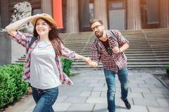 Den attraktiva unga kvinnliga turisten går framåtriktat Hon ler Hållpojkväns för ung kvinna hand och hatt på här huvudet på arkivbild