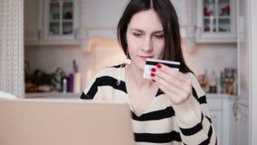 Den attraktiva unga le kvinnan använder den plast- kreditkorten som direktanslutet shoppar med bärbara datorn glidare till rätten arkivfilmer