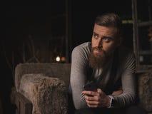 Den attraktiva unga mannen använder en telefon royaltyfria foton