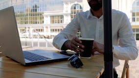 Den attraktiva unga mannen med ett skägg i en vit skjorta sitter på gatan i ett kafé öppnar en bärbar dator och tar en smutt av t stock video