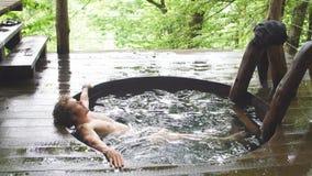 Den attraktiva unga mannen med lockigt ganska hår kopplar av i förkylningen badar arkivfilmer