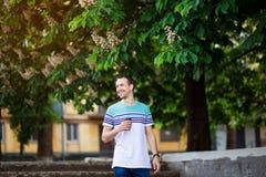 Den attraktiva unga mannen med m?rkt h?r g?r gatan med en kopp kaffe p? en solig dag arkivbild
