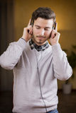 Den attraktiva unga mannen som lyssnar till musik på hörlurar, ögon stängde sig Royaltyfri Bild