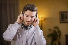 Den attraktiva unga mannen som lyssnar till musik på hörlurar, ögon stängde sig Royaltyfria Foton