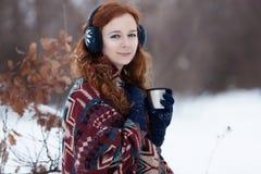Den attraktiva unga rödhåriga kvinnan som dricker en varm drink från en råna i vintern, parkerar Royaltyfria Bilder