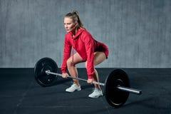Den attraktiva unga sportiga kvinnan utarbetar i idrottshall Den muskulösa kvinnan squatting med skivstången royaltyfri foto