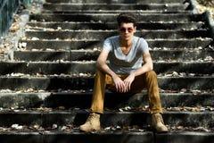 Den attraktiva unga stiliga manen, modellerar av danar i trappa Royaltyfri Foto