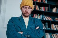 Den attraktiva vuxna människan uppsökte den ilskna manhipsteren i gula hattblickar på kameran och plöjde hans krön på bokväggbakg royaltyfri fotografi