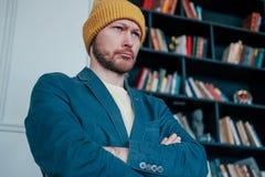 Den attraktiva vuxna människan uppsökte den ilskna manhipsteren i gula hattblickar på kameran och plöjde hans krön på bokväggbakg arkivfoto