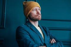 Den attraktiva vuxna människan uppsökte den ilskna manhipsteren i gula hattblickar på kameran och plöjde hans krön på blå väggbak royaltyfri fotografi