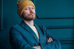 Den attraktiva vuxna människan uppsökte den ilskna manhipsteren i gula hattblickar på kameran och plöjde hans krön på blå väggbak royaltyfria bilder